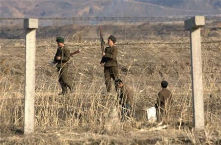 North Korean soldiers guard behind a border fence separating the North Korean town of Sinuiju and the Chinese border city of Dandong, March 23, 2010. REUTERS/Jacky Chen