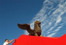 """<p>Um funcionário dá os últimos retoques no leão de ouro, símbolo do Festival de Filmes de Veneza, que inicia na quarta-feira nesta cidade no nordeste da Itália. O festival começa com """"Cisne Negro"""", em que Natalie Portman interpreta uma bailarina de Nova York que vê sua posição ameaçada por uma bela recém-chegada. 30/08/2010 REUTERS/Alessandro Bianchi</p>"""