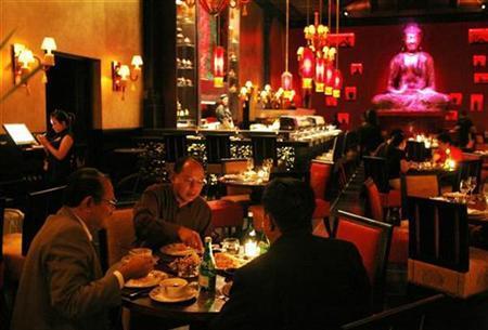 People enjoy their dinner at Buddha Bar Restaurant in Jakarta December 4, 2008. REUTERS/Beawiharta