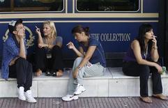 <p>People smoke outside of a shop window in Athens' main business district September 1, 2010. REUTERS/John Kolesidis</p>