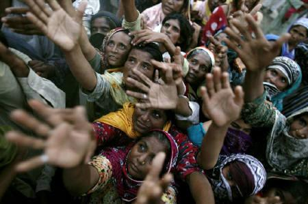 Flood victims left without receiving aid for three days reach for food handouts donated by a group calling themselves Muslim brothers in Pakistan's Muzaffargarh district of Punjab province September 2, 2010. REUTERS/Damir Sagolj