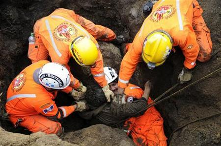 Workers remove a landslide victims in La Cumbre de Alaska September 5, 2010. REUTERS/Stringer