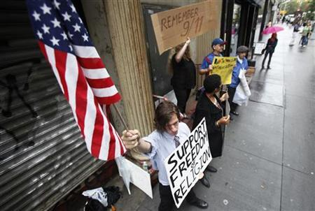 Demonstrators who support and oppose the proposed Muslim cultural center and mosque Park51 stand with signs in front of the site in New York in this August 25, 2010 file photo. REUTERS/Lucas Jackson