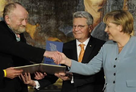 Danish cartoonist Kurt Westergaard (L), whose drawings of Mohammed offended Muslims worldwide, is congratulated on his prize by German Chancellor Angela Merkel (R) during the award ceremony of the M100 media prize 2010 in Potsdam, September 8, 2010. REUTERS/Odd Andersen/Pool