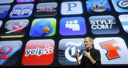 Apple Inc. CEO Steve Jobs speaks in front of the display showing buttons of various apps during the iPhone OS4 special event at Apple headquarters in Cupertino, California April 8, 2010. REUTERS/Robert Galbraith