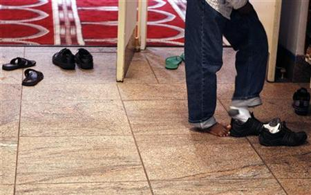 A man removes his shoes before entering the prayer hall at the Islamic Cultural Center of New York in the Manhattan borough of New York August 26, 2010. REUTERS/Lucas Jackson