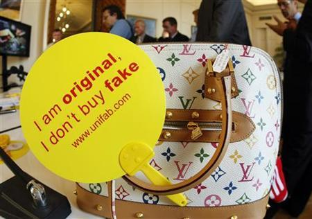 A campaign slogan, 'I am original, I don't buy fake' is displayed on a counterfeit Louis Vuitton luxury handbag by French Customs officers before a destruction operation in Cannes, southeastern France September 28, 2009. REUTERS/Eric Gaillard