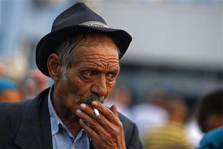 An elderly Roma man smokes after he arrives at Baneasa international airport in Bucharest from Marseille, in the latest wave of what French President Nicholas Sarkozy's government calls a voluntary repatriation scheme, September 14, 2010. REUTERS/Bogdan Cristel