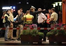 <p>Полиция и работники больницы города Лёррах, Германия 19 сентября 2010 года. Четыре человека погибли и один получил серьезные ранения после того, как вооруженная женщина устроила перестрелку в больнице города Лёррах на юге Германии. REUTERS/Christian Hartmann</p>
