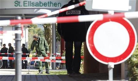 Police officers inspect the area next to the Elisabethen-Krankenhaus hospital in the southern German town of Loerrach September 20, 2010. REUTERS/Christian Hartmann
