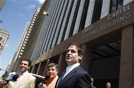 Dallas Mavericks team owner Mark Cuban (C) jokes with reporters as he leaves the Earle Cabell Federal Court building after attending a hearing held to address the insider trading suit filed against him by the Securities and Exchange Commission in Dallas, Texas May 26, 2009. REUTERS/Jessica Rinaldi
