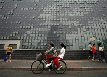 Residents pass a LED display combined with China's first photovoltaic system integrated into a glass wall with solar technology outside a hotel in Beijing in this picture taken July 7, 2010. REUTERS/Bobby Yip