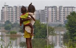 <p>Crianças indianas são vistas perto de inundações em frente à vila atlética dos Jogos da Commonwealth, Nova Délhi, 23 de setembro de 2010. REUTERS/Andrew Caballero-Reynolds</p>