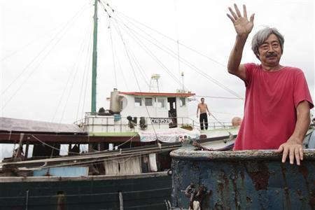 Hong Kong activist Lo Chau (R) waves before setting sail on a fishing boat in Hong Kong for the second time in two days to the disputed Diaoyu Islands September 23, 2010. REUTERS/Tyrone Siu