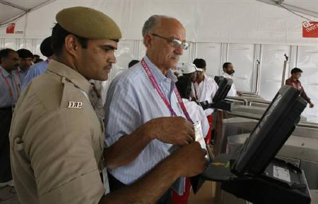 Commonwealth Games Federation President Michael Fennell (C) waits to go through the security barriers at the Commonwealth Games athletes village in New Delhi September 27, 2010. REUTERS/Amit Dave