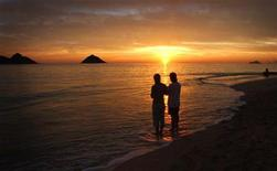 <p>A couple watches the sunrise at the Mokulua Islands bird sanctuary, on Lanikai Beach in Kailua, Hawaii in this December 17, 2004 file photo. REUTERS/Lucy Pemoni</p>
