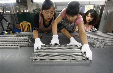 Employees inspect newly made products at an automobile components factory in Suining, Sichuan province September 1, 2010. REUTERS/Stringer
