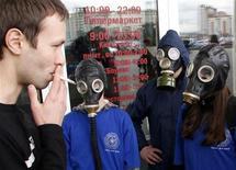 <p>Группа молодых людей в противогазах на акции протеста против курения в Красноярске 1 мая 2010 года. Российские власти намерены полностью запретить рекламу табака к 2012 году, а курение в общественных местах - к 2015 году, пытаясь победить вредную привычку в стране, где курит более половины взрослого населения. REUTERS/Ilya Naymushin</p>