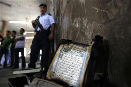 A partially burnt Koran is laid against the wall of a mosque that was vandalized in the West Bank village of Beit Fajjar near Bethlehem October 4, 2010. REUTERS/Ammar Awad