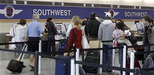 <p>Люди стоят в очереди к билетной стойке Southwest Airlines в аэропорту Мидуэй в Чикаго 27 сентября 2010 года. Пассажиры международных авиарейсов не хотят, чтобы самообслуживание ограничивалось онлайн-бронированием билетов и регистрацией на рейс в аэропорту. REUTERS/Frank Polich</p>
