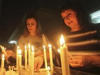 <p>Worshippers light candles after attending a weekly mass at Sacred Heart Catholic Church in Baghdad October 3, 2010. REUTERS/Mohammed Ameen</p>