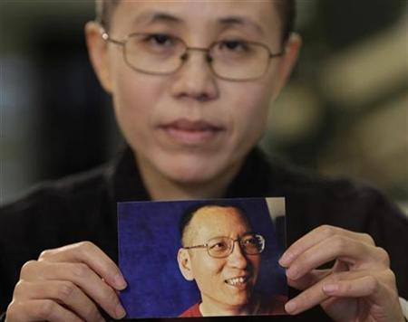 Liu Xia, the wife of Chinese dissident Liu Xiaobo, holds a photo of her husband during an interview in Beijing, October 3, 2010. REUTERS/Petar Kujundzic