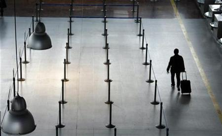 A passengers walks past empty counters in a file photo. REUTERS/Eric Gaillard