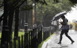 <p>A woman walks with an umbrella amid a downpour on New York City's upper West side October 1, 2010. Torrential rain and wind lashed the East Coast on Friday snarling traffic and triggering tornado watches and flood warnings. REUTERS/Mike Segar</p>