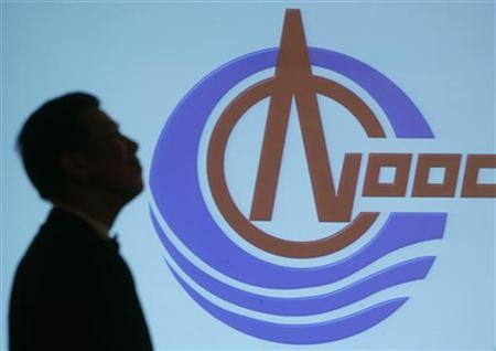 A man walks past a screen with the projected logo of CNOOC Ltd. during a news conference for the 2006 annual results announcement in Hong Kong March 29, 2007. REUTERS/Paul Yeung