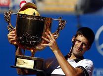 <p>Novak Djokovic segura troféu após derrotar David Ferrer no Aberto da China. 11/10/2010 REUTERS/David Gray</p>
