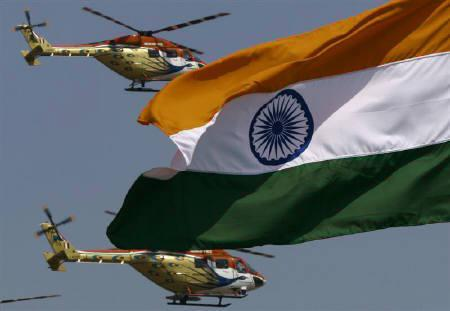 India's national flag flutters as Indian Air Force helicopters perform during an air show in Bangalore February 11, 2009. REUTERS/Vijay Mathur/Files