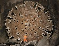 <p>A miner stands in front of the drill machine 'Sissi' after it broke through the rock at the final section Faido-Sedrun, at the construction site of the NEAT Gotthard Base Tunnel October 15, 2010. REUTERS/Christian Hartmann</p>