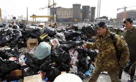 An army officer walks past a pile of garbage in downtown Naples October 22, 2010. REUTERS/Agnfoto