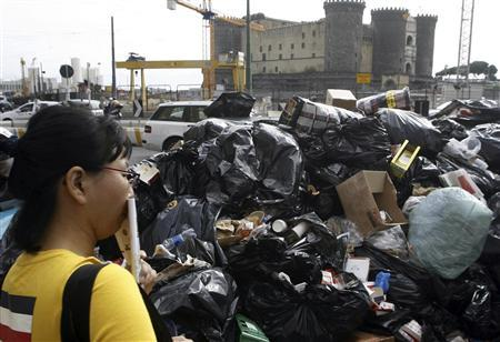 A woman covers her mouth near a pile of garbage in downtown Naples October 22, 2010. REUTERS/Agnfoto