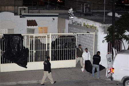 Forensic workers carry a body at a crime scene in Ciudad Juarez October 23, 2010. REUTERS/Gael Gonzalez