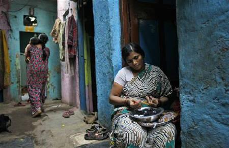 Shobha Vakade, 28, who took a loan of rupees 18,000 ($400) from a micro finance company to start her own business, strings beads into necklaces outside her house in a slum in Mumbai October 26, 2010.  REUTERS/Danish Siddiqui