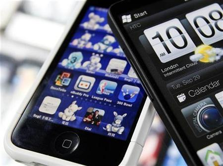 A HTC smartphone (R) and an Apple iPhone are displayed for the photographer at a mobile phone shop in Taipei March 3, 2010. REUTERS/Nicky Loh