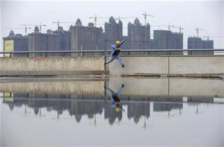 A worker jumps over a puddle near a residential construction site in Taiyuan, Shanxi province October 26, 2010. REUTERS/Stringer
