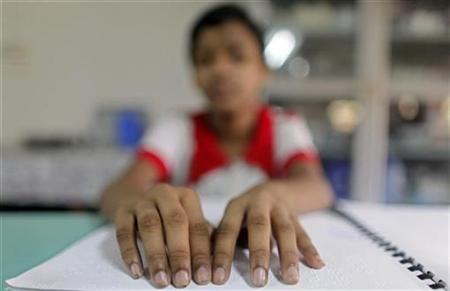 A visually impaired boy takes part in a lesson in Dhaka, May 19, 2010. REUTERS/Andrew Biraj