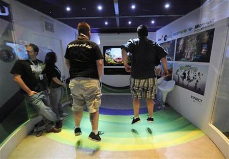 Attendees play Kinect Adventures for Microsoft Xbox in an enclosed booth at the E3 Media & Business Summit in Los Angeles June 16, 2010. REUTERS/Phil McCarten