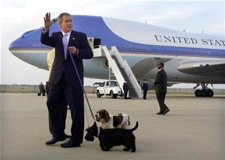 President George W. Bush waves to the press while holding the family dogs ''Barney'' (foreground) and ''Spot'' (rear) after he and [first lady Laura Bush] arrived at a Waco, Texas airport, November 13, 2001. REUTERS/Jeff Mitchell