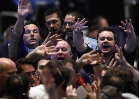 Traders in the 30-year bond options pit at the Chicago Board of Trade signal orders shortly after the Federal Reserve's decision to leave short-term interest rates untouched, November 3, 2010. REUTERS/Frank Polich