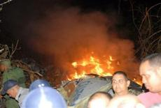 <p>Rescue workers are seen beside the burning remains of an ATR-72-212 twin turboprop aircraft which crashed near Guasimal in central Cuba November 4, 2010. REUTERS/Escambray Daily/Courtesy of Cubadebate/Handout</p>