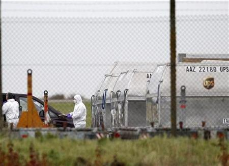 A forensic officer removes a package from a UPS container at East Midlands Airport in Castle Donington, central England October 29, 2010. REUTERS/Darren Staples