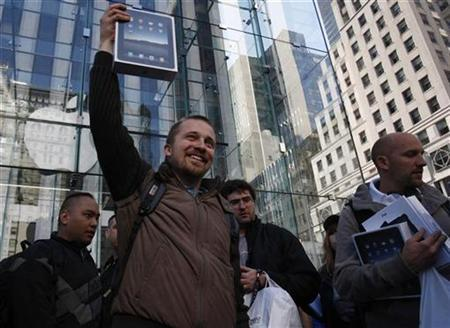 A customer lifts his iPad over his head after leaving the iPad launch at the Apple Store in New York April 3, 2010. REUTERS/Jessica Rinaldi