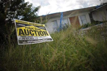 An auction sign for a property is seen at the front garden of a foreclosed house in Miami Gardens, Florida, September 15, 2009. REUTERS/Carlos Barria