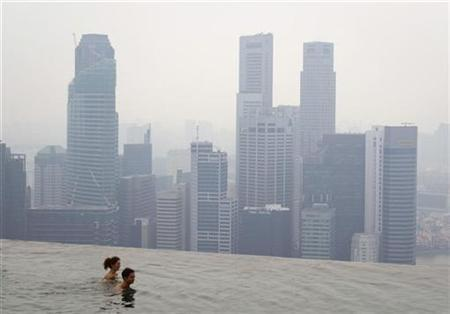 Hotel guests swim in an infinity pool overlooking the haze-covered skyline in Singapore October 22, 2010. REUTERS/Vivek Prakash