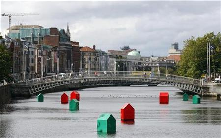 An art installation of Monopoly houses and hotels by Irish contemporary artist Fergal McCarthy floats on the river Liffey in Dublin, September 21, 2010. The installation was designed to highlight the troubled housing market in Ireland. REUTERS/Cathal McNaughton