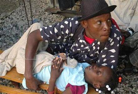 A Haitian resident holds his relative who is suffering from cholera at St-Catherine hospital in the slum of Cite-Soleil in Port-au-Prince November 12, 2010. REUTERS/St-Felix Evens