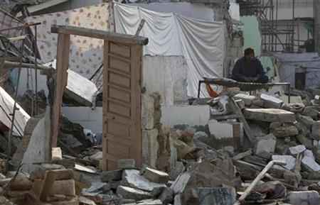 A man sits on a bed amidst the rubble of his levelled home in Karachi November 13, 2010, two days after it was destroyed in a suicide bomb. REUTERS/Akhtar Soomro